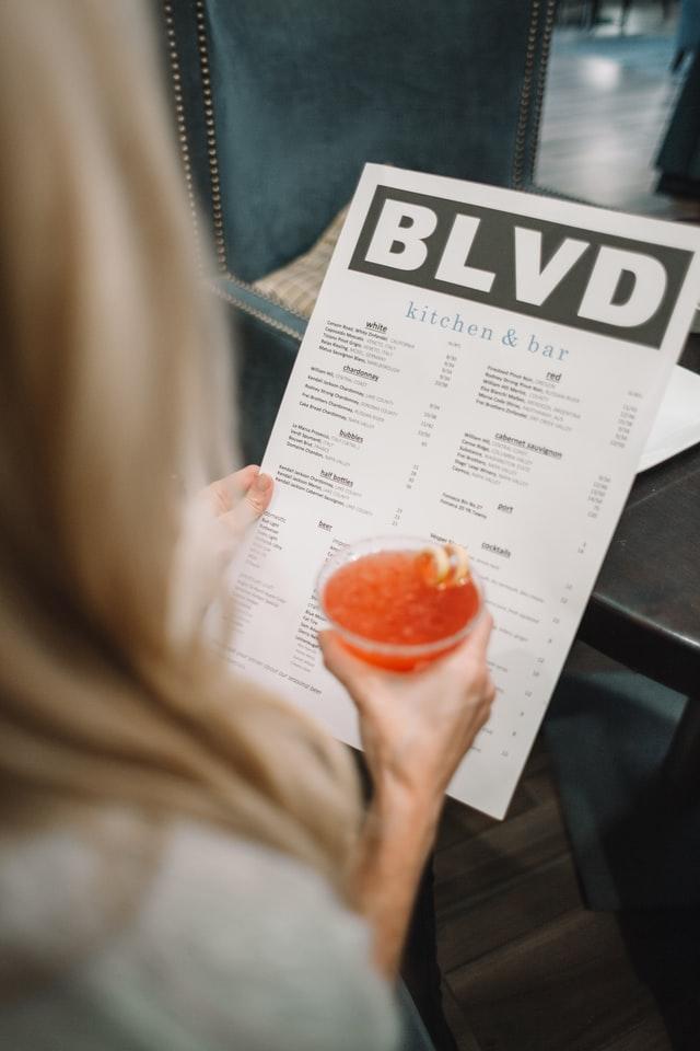 Persona en un restaurante cogiendo una carta física.